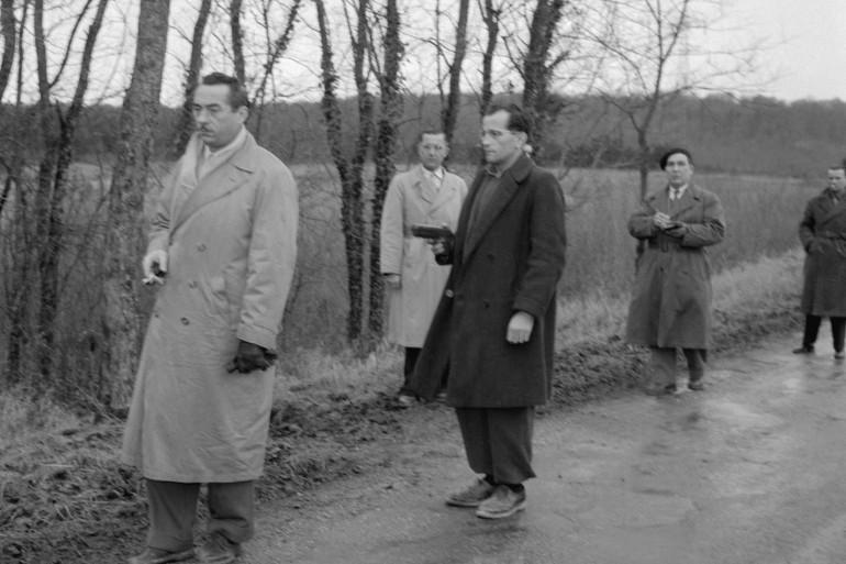 L'Abbé Desnoyers, curé d'Uruffe braque son arme sur un policier qui a pris la place de Régine Fays lors de la reconstitution de son crime, e 07 décembre 1956 à Uruffe.