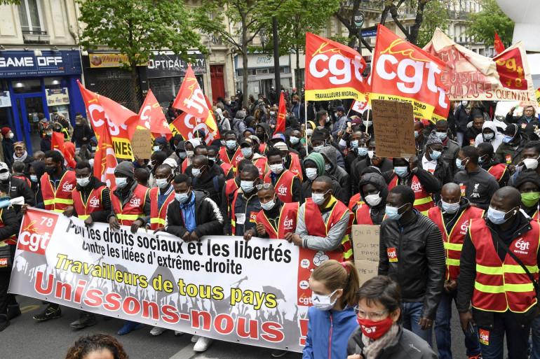 Les manifestants de la CGT brandissent une banderole lors de la manifestation annuelle des travailleurs du 1er mai à Paris, le 1er mai 2021.
