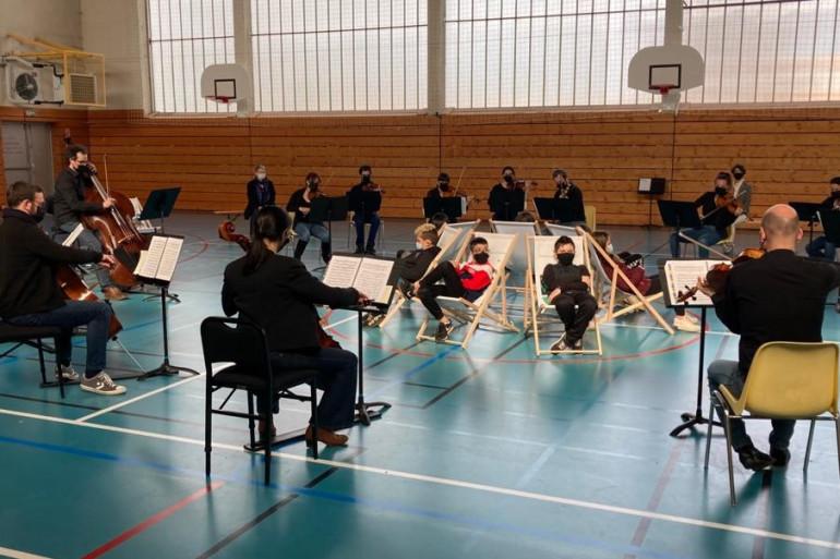 Au milieu du gymnase, ces élèves profitent d'un concert privé de l'orchestre Victor Hugo
