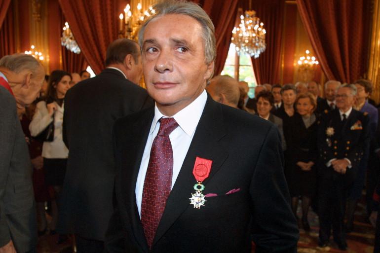 Michel Sardou pose, le 16 novembre 2001 au palais de l'Elysée à Paris, après avoir reçu la décoration d'officier dans l'ordre de la Légion d'Honneur