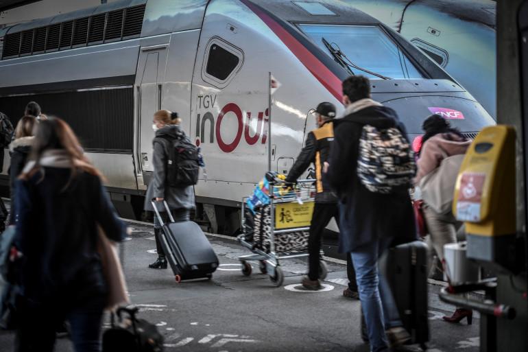 Des voyageurs masqués marchent vers leur train dans le hall des départs de la gare de Lyon à Paris, le 18 décembre 2020, à la veille du début de la période des fêtes. (Illustration)