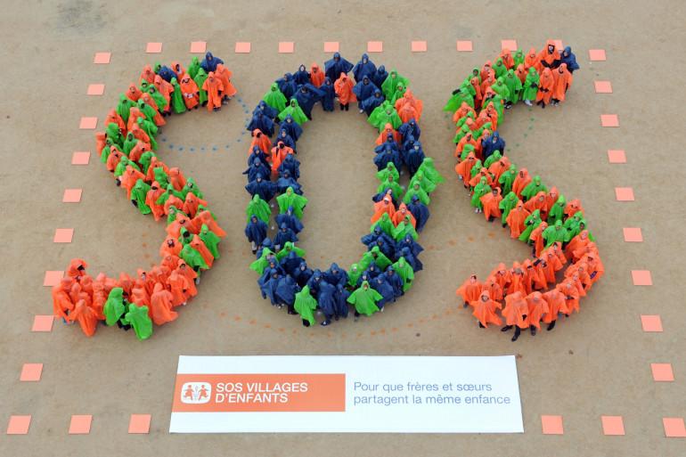 Deux cents écoliers forment un SOS géant avec leurs capes colorées, le 19 novembre 2010 sur le Champ-de-Mars à Paris lors d'un événement organisé par l'association SOS Villages d'enfants. (Illustration)
