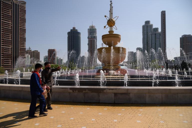 Un homme et un enfant marchent devant une fontaine à Pyongyang, le 25 avril 2021.