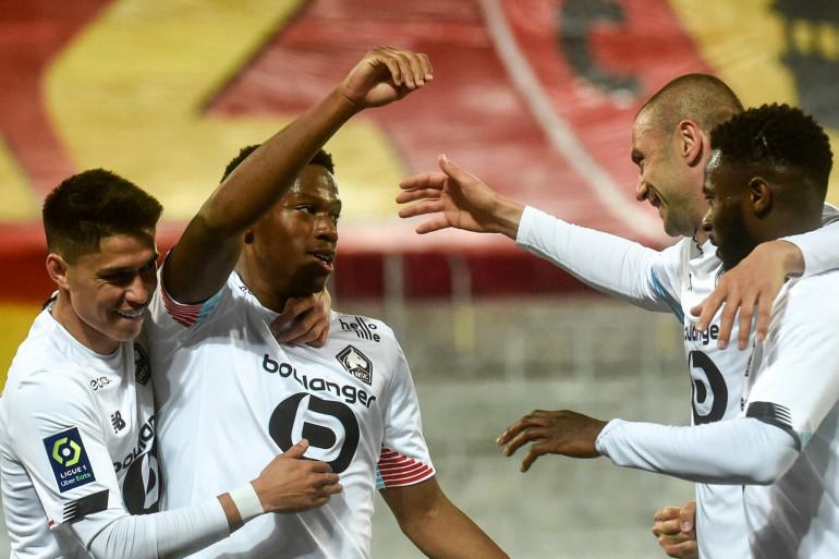L'attaquant de Lille Jonathan David (2e L) célèbre la victoire avec ses coéquipiers à Lens, le 7 mai 2021.