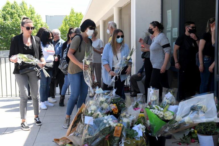 Des gens apportent des fleurs devant le commissariat d'Avignon, le 9 mai 2021, en hommage au policier Eric Masson, tué le 5 mai lors d'une opération anti-drogue.