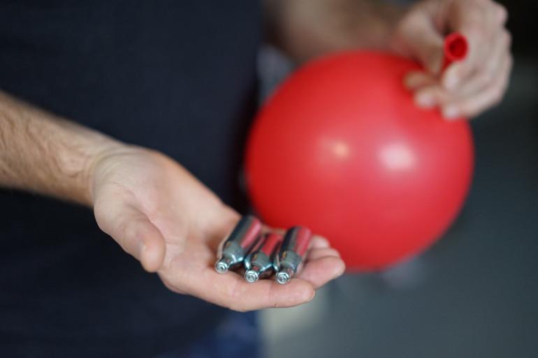 Les usagers du gaz hillarant ouvrent les cartouches pour en récupérer le gaz et le déverser dans un ballon, avant de le respirer.