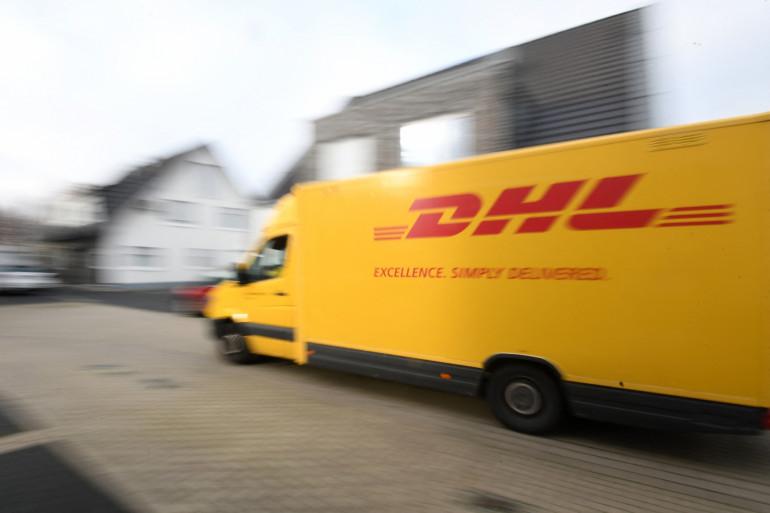 Photo d'une camionnette de la société DHL qui livre des colis dans un quartier résidentiel de Dortmund, dans l'ouest de l'Allemagne, le 10 décembre 2020. (Illustration)