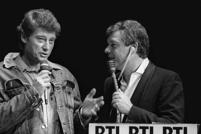 """Le chanteur français, Johnny Hallyday, participe à l'émission de RTL """"Casino Parade"""", en compagnie de l'animateur Fabrice, en direct du Théâtre Montparnasse, le 10 octobre 1983, à Paris"""