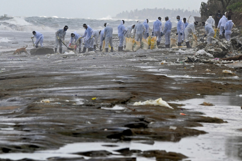 Membres de la Navy Sri-lankaise enlevant les débris laissés par l'incendie à bord du porte-conteneurs MV X-Press Pearl au large de Cobombo, 31 mai 2021