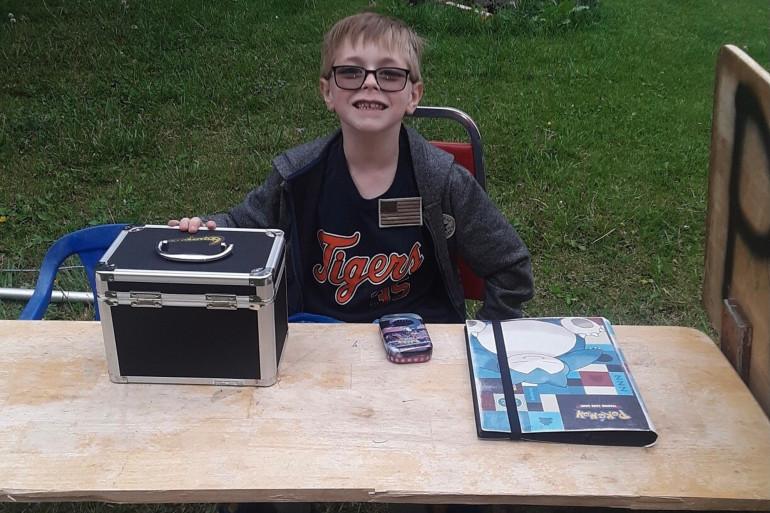 Bryson devant son stand de cartes Pokémon