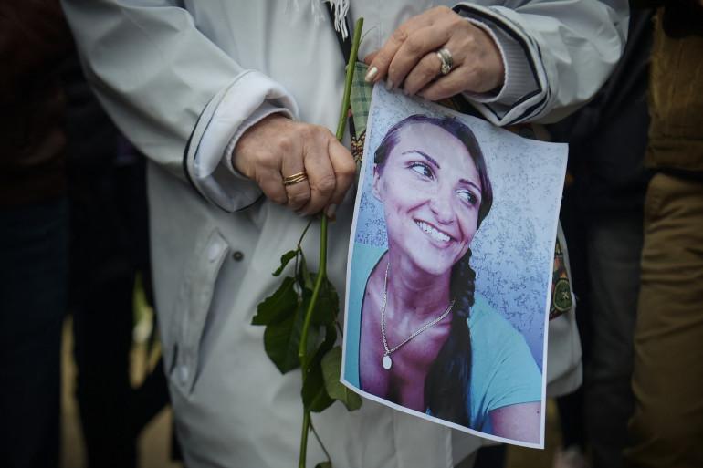Une femme tient une photo de Julie Douib, lors d'une marche commémorative le 9 mars 2019