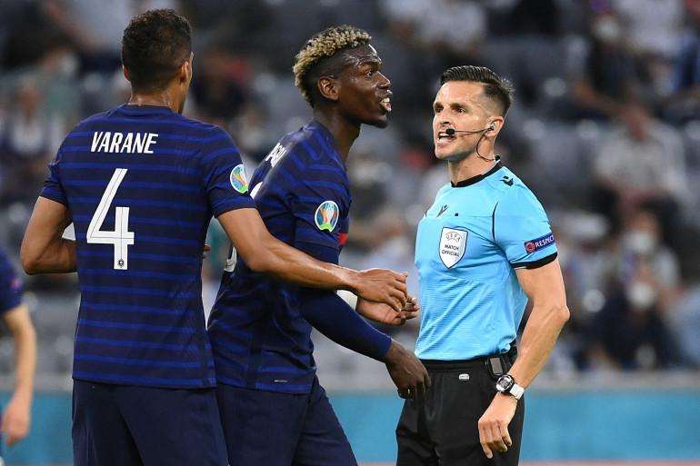 L'arbitre espagnol Carlos Del Cerro Grande (D) s'entretient avec Paul Pogba (C) lors du match du groupe F de l'UEFA Euro 2020 entre la France et l'Allemagne à Munich, le 15 juin 2021.
