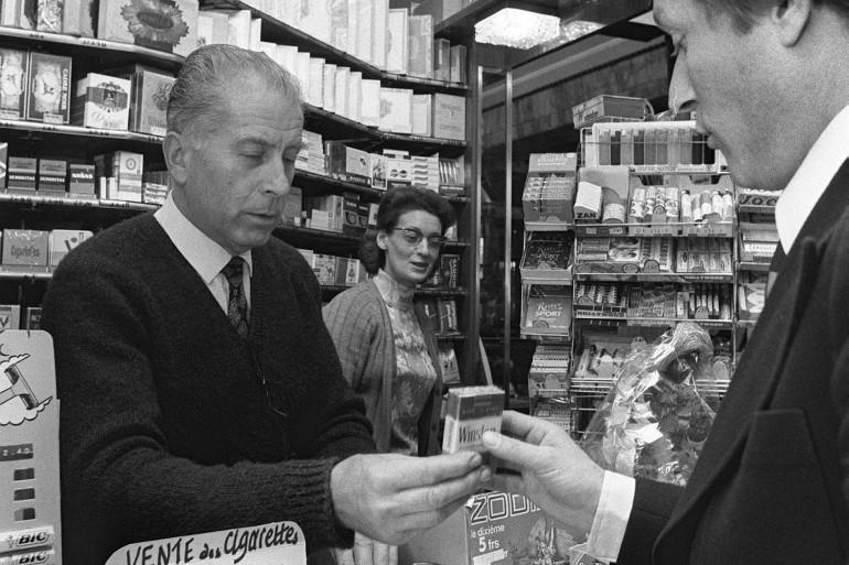 Un client achète le 13 mai 1975, un paquet de cigarettes chez un buraliste, à Paris. (illustration)