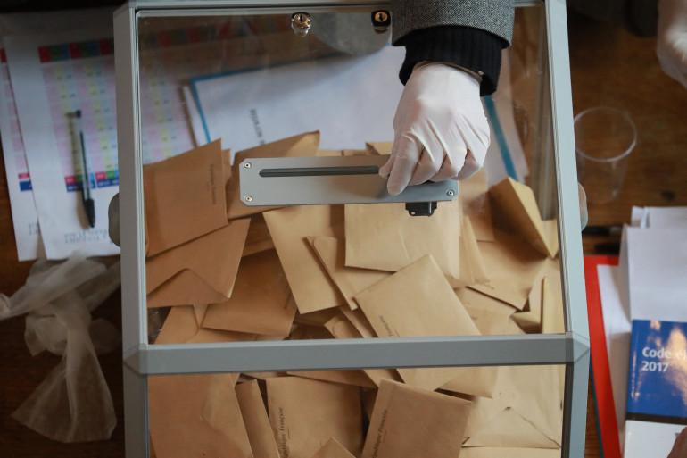 Un assesseur avec la main gantée lors de l'élection municipale de 2020 (illustration)