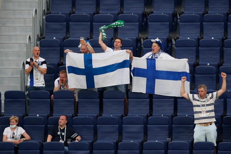 Des supporters finlandais agitent le drapeau national avant le match de football du groupe B de l'Euro entre la Finlande et la Belgique, au stade de Saint-Pétersbourg, en Russie, le 21 juin 2021.