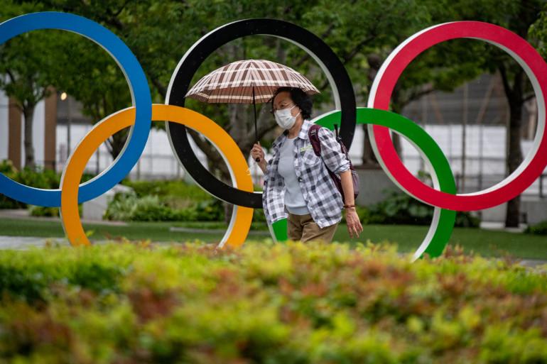 Une Japonaise devant les anneaux olympiques le 8 juillet 2021
