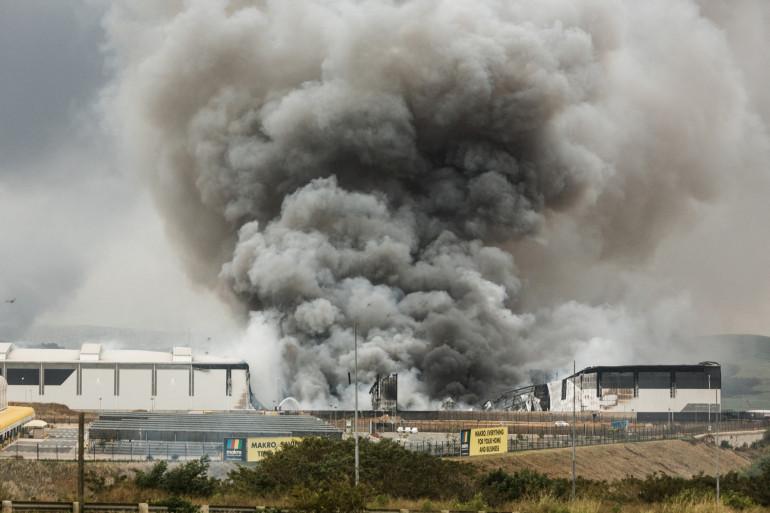 De la fumée s'élève d'un bâtiment de Makro incendié pendant la nuit à Umhlanga, au nord de Durban, en Afrique du Sud, le 13 juillet 2021, après quatre nuits de violence déclenchées par l'emprisonnement de l'ex-président Jacob Zuma.