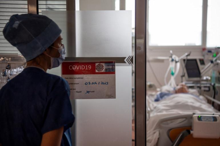 Un membre du personnel médical regarde un patient infecté par le Covid-19 allongé sur un lit à l'unité de soins intensifs (USI) de l'hôpital privé Elsan - Clinique Océane à Vannes, dans l'ouest de la France, le 20 avril 2021. (Illustration)