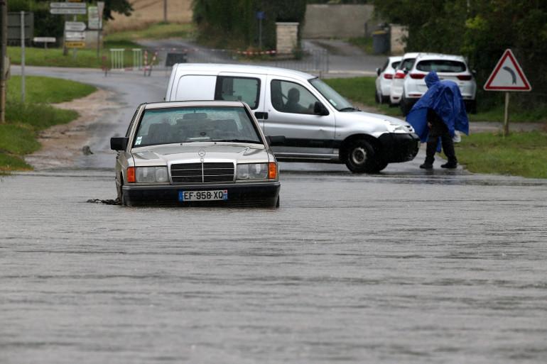 Une voiture coincée dans l'eau le 15 juillet 2021 près des rives inondées de la rivière Ardre à Fismes, dans l'est de la France.