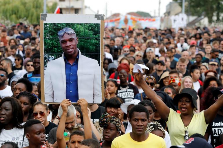 Photo d'une personne qui tient un portrait d'Adama Traoré lors d'une marche pour réclamer des réponses,  deux ans après sa mort en garde à vue, le 21 juillet 2018 à Beaumont-sur-Oise, au nord-est de Paris. (Illustration)