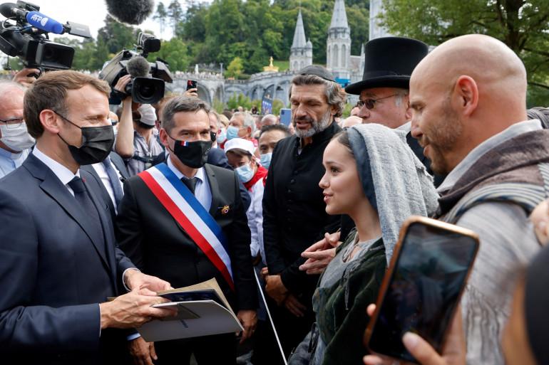 Emmanuel Macron rencontre les chanteurs d'une comédie musicale de théâtre avec le maire de Lourdes Thierry Lavit, lors d'une visite au sanctuaire catholique de Notre-Dame-de-Lourdes, dans le sud-ouest de la France, le 16 juillet 2021.