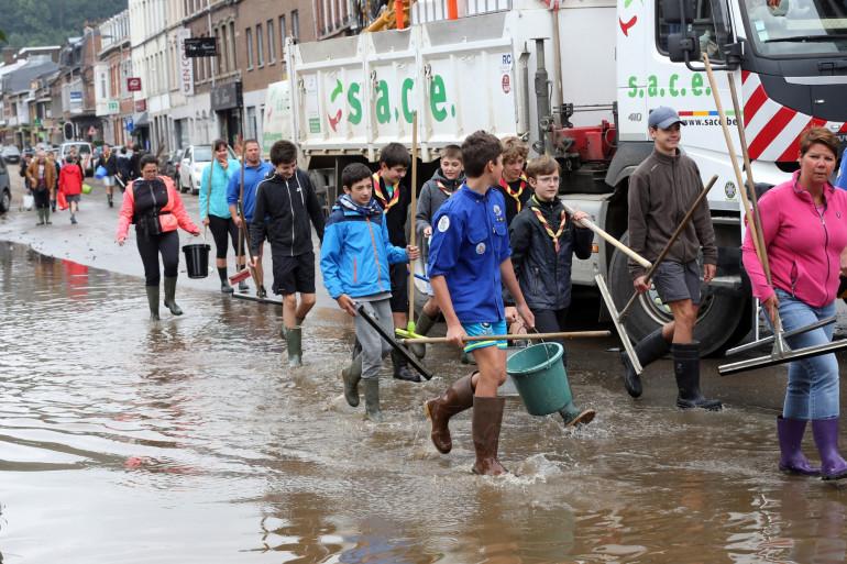 Des scouts marchent dans une rue inondée de Pepinster le 16 juillet 2021, où la situation reste critique après les fortes pluies des jours précédents.