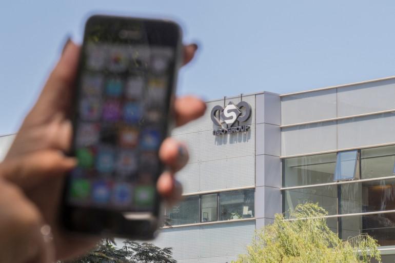 """Illustration d'un smartphone devant la siège de NSO, entreprise ayant développé le logiciel """"Pegasus"""", à Herzliya, près de Tel Aviv."""