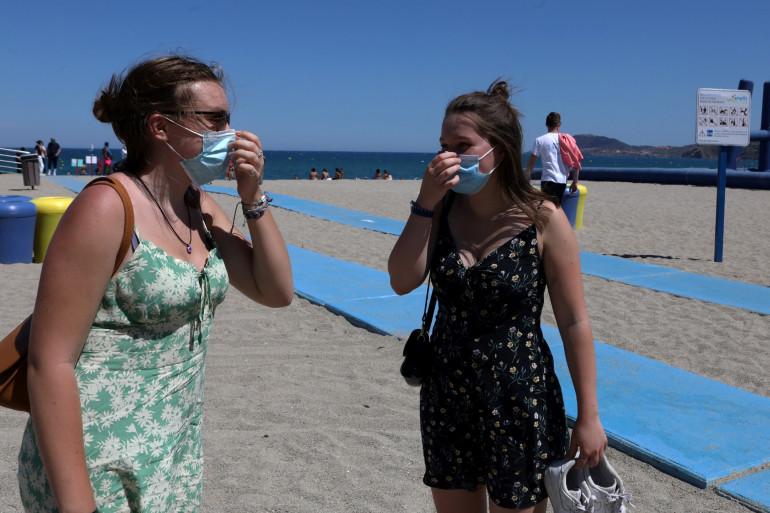 Des vacancières remettent leur masque en quittant la plage à Argelès-sur-Mer (Pyrénées-Orientales).
