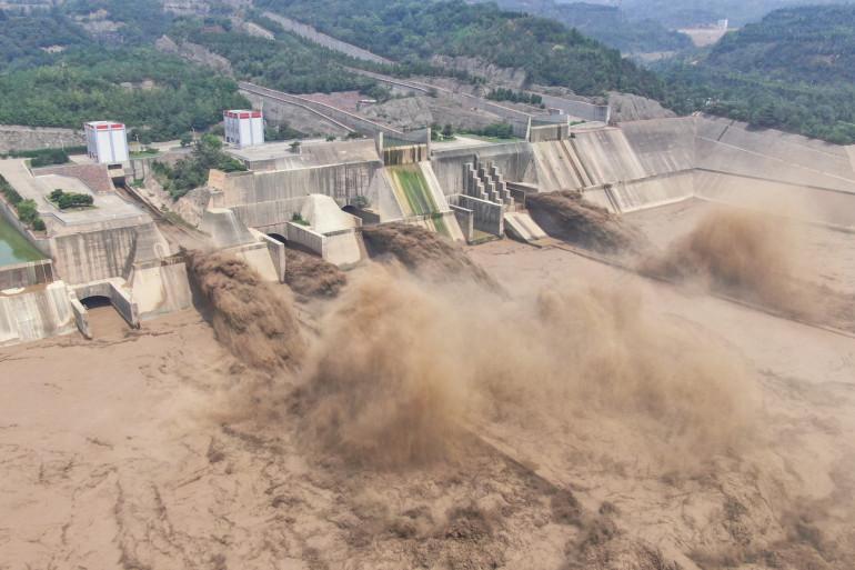 Photo aérienne prise le 5 juillet 2021 montrant l'eau s'échappant du barrage de Luoyang dans la province chinoise du Henan