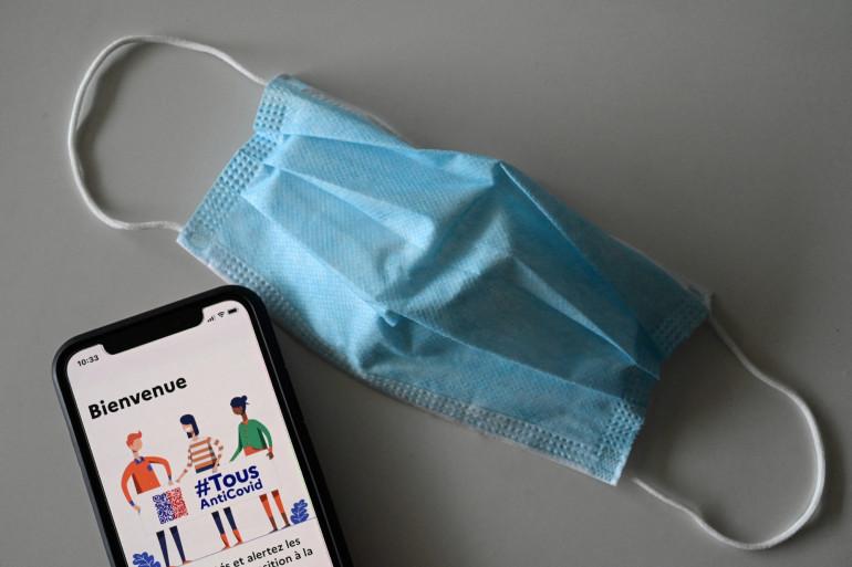 Cette photo prise le 12 février 2021, à Montpellier, montre un masque et un téléphone portable connectés à l'application de suivi #TousAntiCovid. (Illustration)