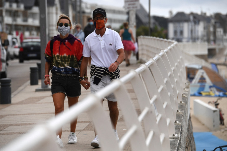 Un couple portant un masque le long du front de mer, le 27 juillet 2020 à Quiberon.