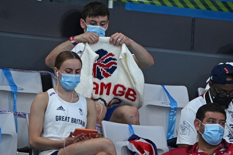 Tom Daley en tribune avec un pull tricoté lors lors du tour préliminaire du plongeon masculin au JO de Tokyo, le 2 août.