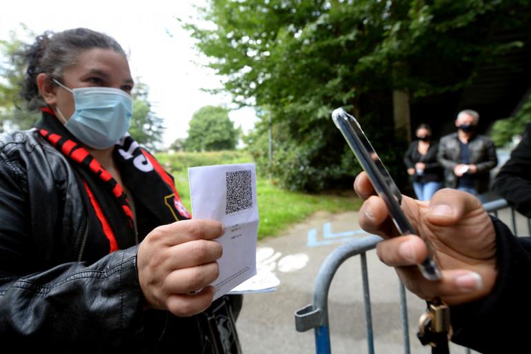 Une supportrice montre son passe sanitaire avant le match entre le Stade Rennais et le RC Lens à Rennes, le 8 août 2021.
