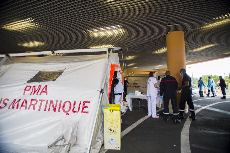 Pompiers et secouristes devant une tente de triage mise en place pour soigner les patients, au CHU Pierre Zobda-Quitman de Fort-de-France le 30 juillet 2021.