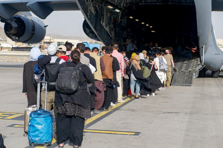 Des Afghans en train d'embarquer dans un avion militaire ce vendredi 20 août