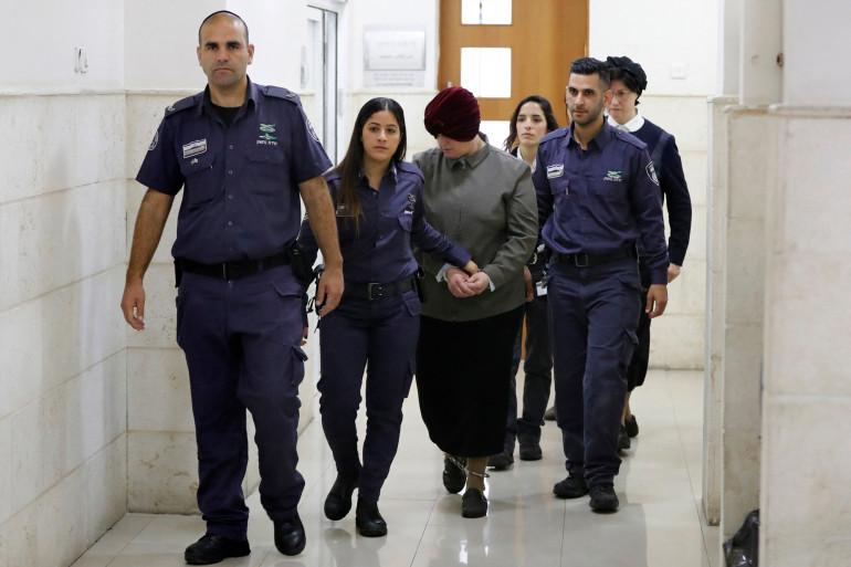 Photo de Malka Leifer, ancienne directrice d'école australienne accusée de pédophilie, escortée par la police alors qu'elle arrive pour une audience au tribunal de Jérusalem le 27 février 2018.