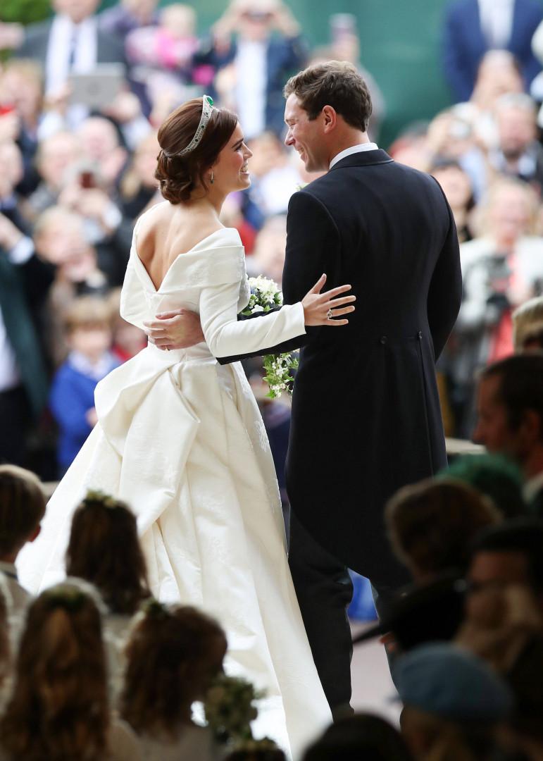 Le couple de jeunes mariés de dos depuis la chapelle après la cérémonie
