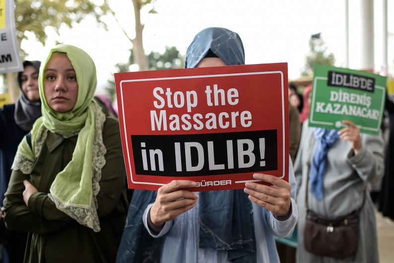 """Une femme porte une pancarte : """"Stop au massacre à Idelb"""""""