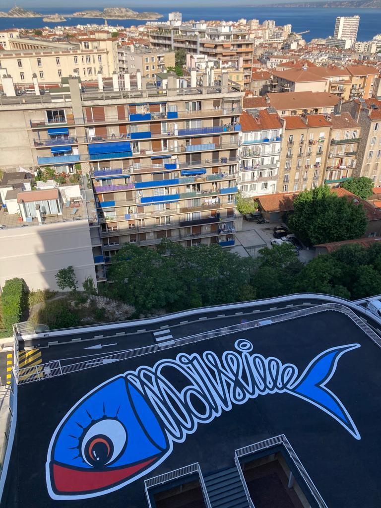 Son corps est constitué du mot Marseille, la queue et la tête sont bleues, un grand œil pétillant et la lèvre écarlate.