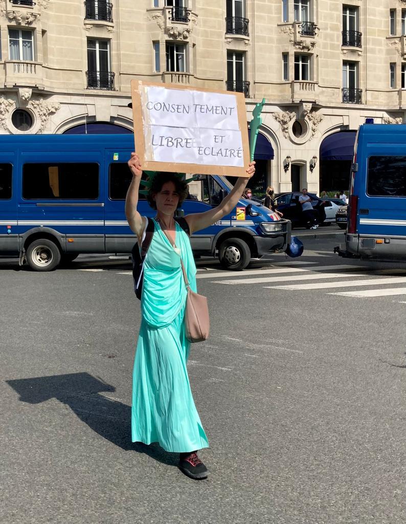 """Une manifestante contre le vaccin brandissant une pancarte """"Consentement libre et éclairé"""", à Paris ce samedi 17 juillet 2021"""