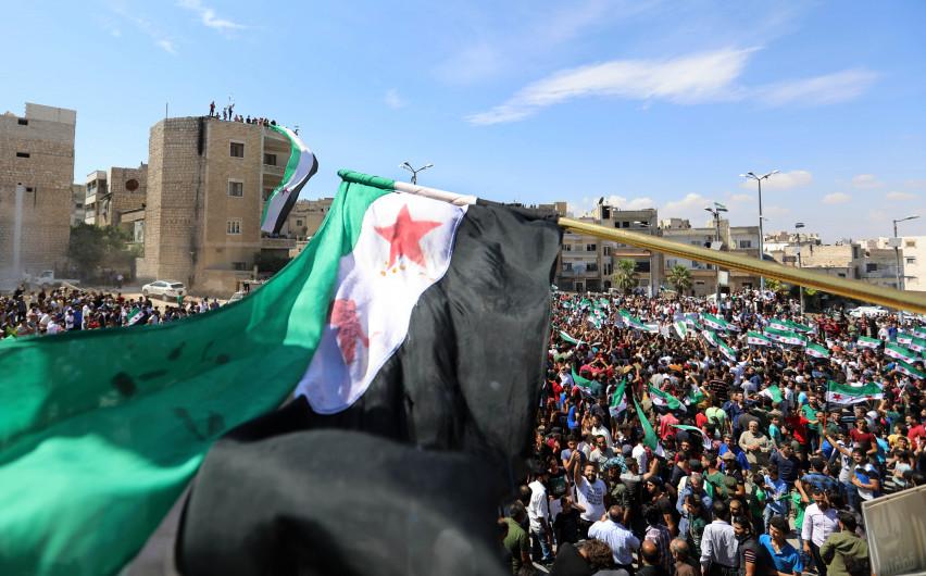 Un énorme drapeau de l'opposition agité au-dessus de la foule à Idleb