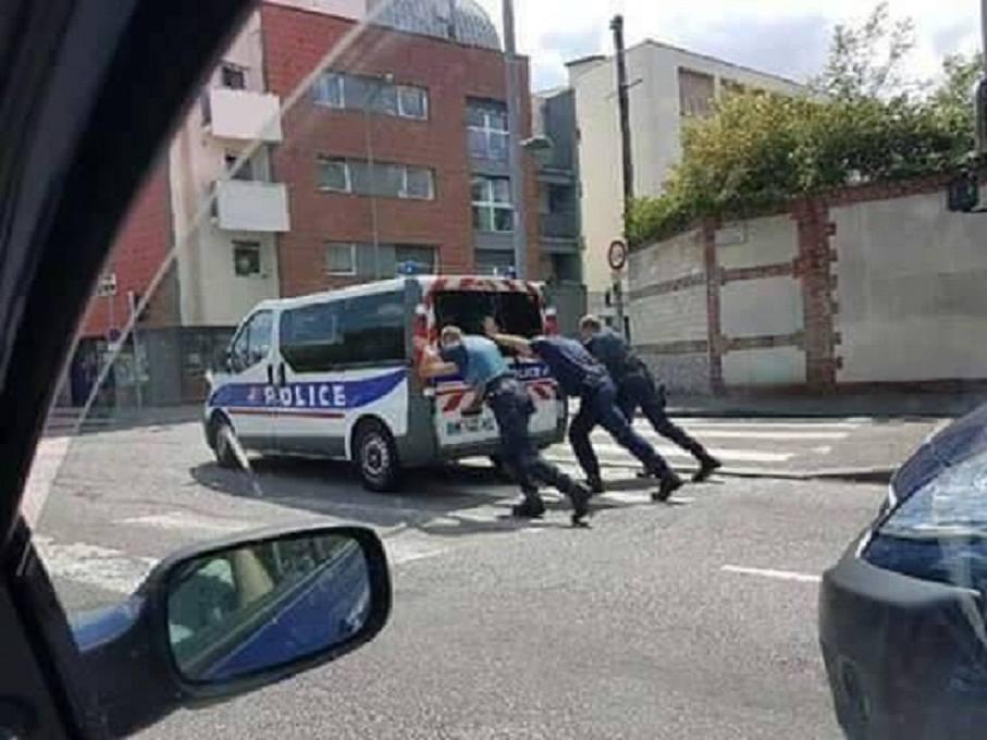 Des policiers en train de pousser leur véhicule en pleine rue