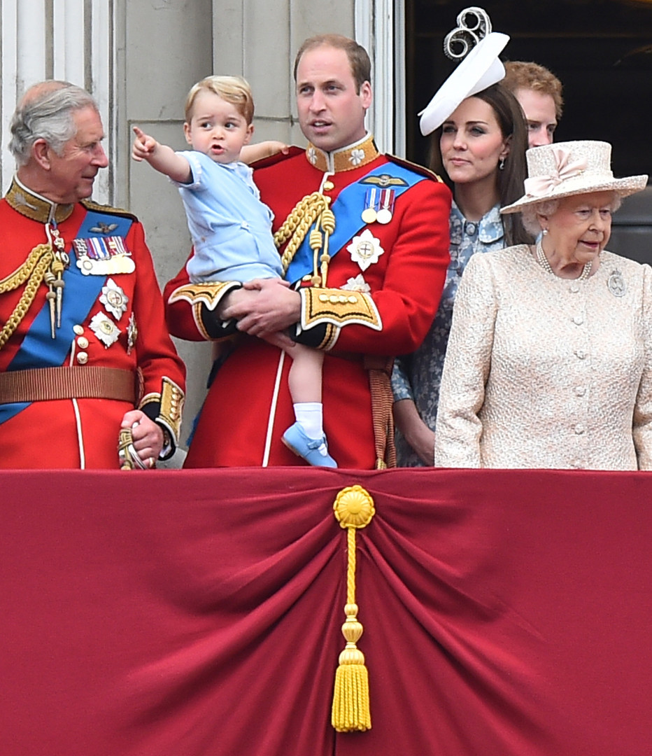 Le prince George dans les bras de son père sous l'œil attentif de sa mère