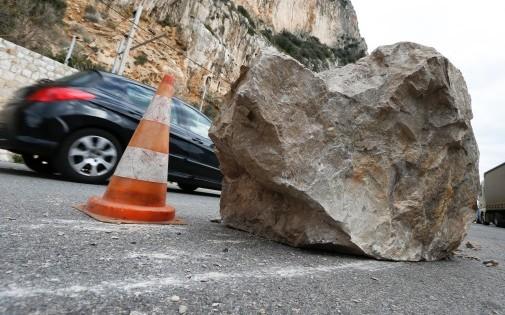 Une voiture passe derriere un rocher tombé suite à un éboulement arrachant des caténaires, à Beaulieu-Sur-Mer le 10 février 2013.