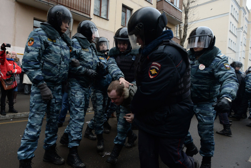 Des policiers anti-émeutes arrêtent des protestataires devant le tribunal de Moscou jugeant des manifestants anti-Poutine, le 24 février 2014.