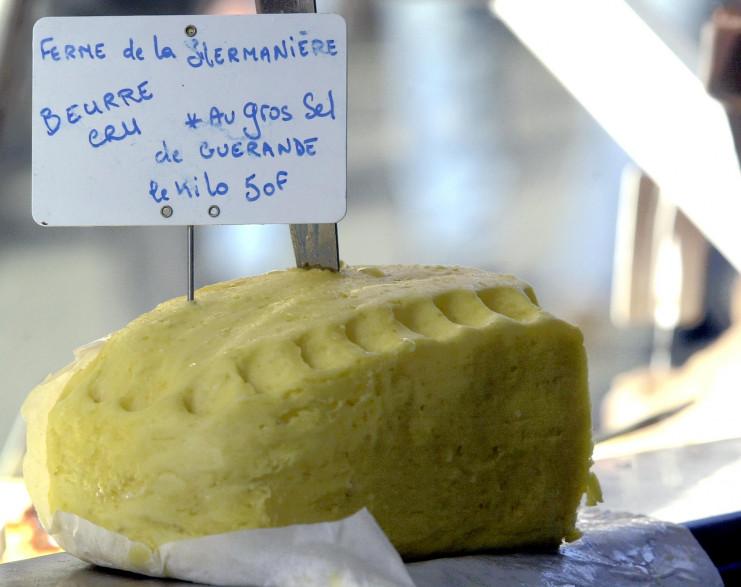 Une motte de beurre cru fermier est présentée sur l'étal d'un producteur fromager sur le marché des fossés Saint Julien à Caen