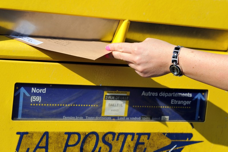 Une habitante de Lille dépose un courrier dans une boîte aux lettres de La Poste, le 10 septembre 2013 (archives)