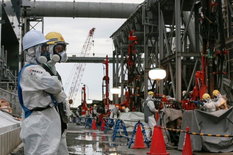 Des ouvriers sur le site de la centrale nucléaire de Fukushima, le 9 juillet 2014 au Japon.