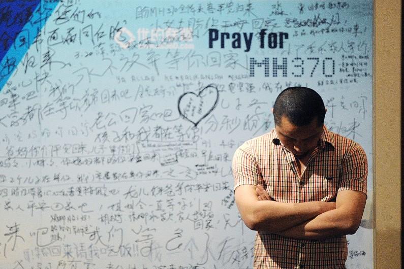 Un homme se tient devant un tableau d'hommages aux victimes du vol MH370 de la Malaysia Airlines, le 23 avril 2014.