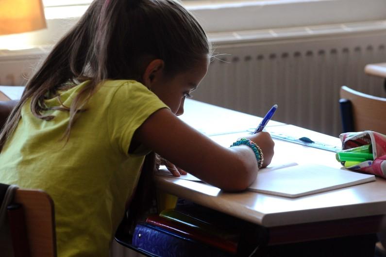 Une élève en train d'écrire (illustration)
